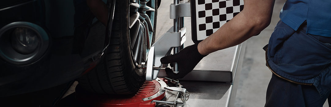 worker checking tire alignment